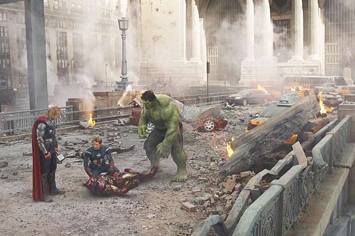 Thor, Captain America and Hulk stand over Iron Man in debris and destruction in NYC